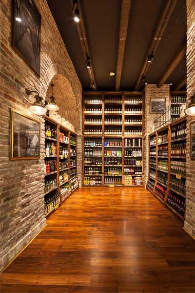 עיצוב חנות למוצרי יין, אדר' מיקלה סימונה. שימוש בקורות עץ דקורטיביות בצבע ונגה.